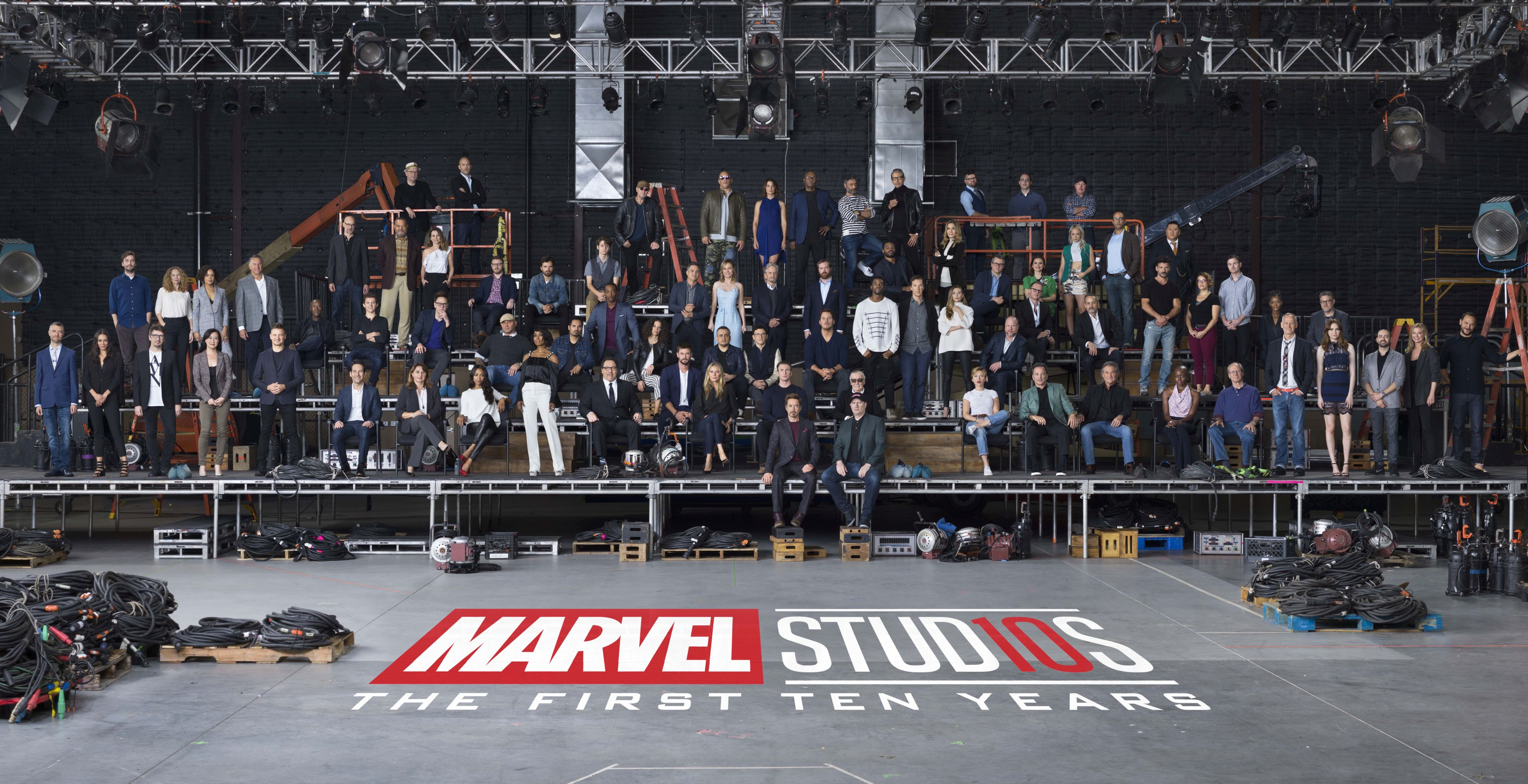 "Marvel Studios ""The First Ten Years"" Class Photo Front Row L to R: Sean Gunn (Kraglin), Hannah John-Kamen (Ghost), Director Scott Derrickson, Executive Producer Trinh Tran, Jeremy Renner (Hawkeye), Paul Rudd (Ant-Man), EVP, Physical Production Victoria Alonso, Zoe Saldana (Gamora), Angela Bassett (Ramonda), Director/Actor Jon Favreau (Happy Hogan), Chris Hemsworth (Thor), Gwyneth Paltrow (Pepper Potts), Chris Evans (Captain America), Robert Downey Jr. (Iron Man), Executive Producer/Writer Stan Lee, President of Marvel Studios Kevin Feige, Scarlett Johansson (Black Widow), Co-President of Marvel Studios Louis D'Esposito, Kurt Russell (Ego), Danai Gurira (Okoye), William Hurt (Thaddeus Ross), Director Alan Taylor, Karen Gillan (Nebula), Executive Producer Brad Winderbaum, Emily VanCamp (Sharon Carter), Director Louis Letterier Second Row L to R: Director Jon Watts, Casting Director Sarah Finn, Tessa Thompson (Valkyrie), VP, Physical Production David Grant, Don Cheadle (War Machine), Tom Holland (Spider-Man), Director James Gunn, Dave Bautista (Drax), Michael Peña (Luis), Anthony Mackie (Falcon), Evangeline Lilly (Wasp), Director Joe Russo, Director Anthony Russo, Chris Pratt (Star-Lord), Chadwick Boseman (Black Panther), Benedict Cumberbatch (Doctor Strange), Elizabeth Olsen (Scarlet Witch), Director Joss Whedon, Paul Bettany (Vision), VP, Physical Production Mitchell Bell, Frank Grillo (Crossbones), Director Anna Boden, Director Ryan Fleck, Letitia Wright (Shuri), Editor Jeffrey Ford Third Row L to R: Director Peyton Reed, Laurence Fishburne (Dr. Bill Foster), Linda Cardellini (Laura Barton), Executive Producer Jonathan Schwartz, Sebastian Stan (Winter Soldier), Ty Simpkins (Harley Keener), Mark Ruffalo (Hulk), Brie Larson (Captain Marvel), Michael Douglas (Hank Pym), Executive Producer Stephen Broussard, Director Ryan Coogler, Michelle Pfeiffer (Janet van Dyne), Executive Producer Jeremy Latcham, Hayley Atwell (Peggy Carter), Pom Klementieff (Mantis), Exe"